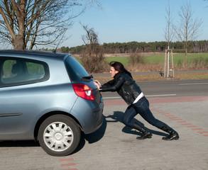 junge frau schiebt ihr auto