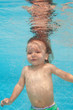 Happy toddler kid diving under water