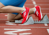 Detailed view of a sprinter in the starting blocks poster
