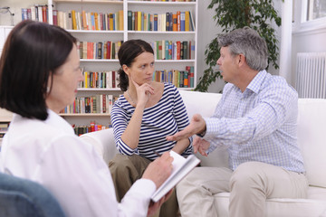 couple arguing during therapy session with psychologist