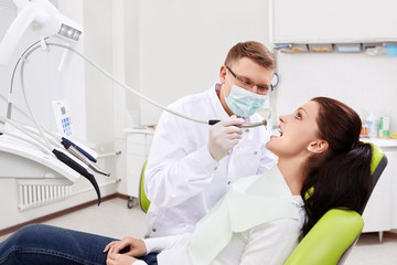 The dentist treats teeth of patient