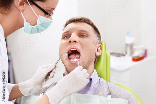 The dentist treats teeth of the man in the dental clinic