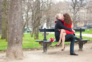 Happy romantic couple hugging and kissing on a bench