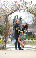 Dating couple hugging under beautiful arch