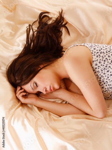 A beautiful woman is sleeping in bed - view above