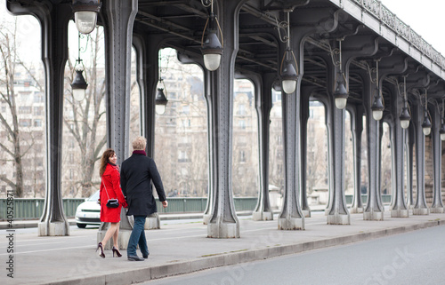Romantic couple walking on the Bir-Hakeim bridge in Paris