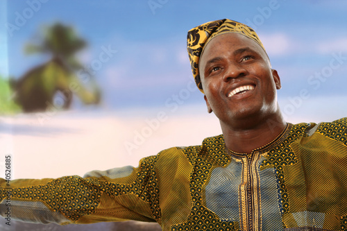 A smiling black man on the beach is looking upwards