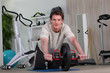 Man using an ab roller (exercise wheel)