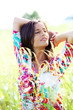 Brunette girl with colorful shirt standing in meadow