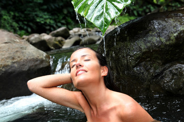 Beautiful girl showering in river under waterfall