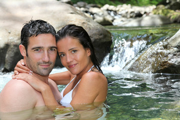 Closeup of cheerful couple bathing in river