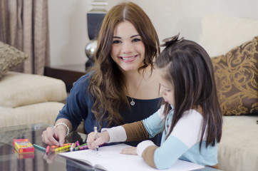 Young mother coloring a book with her daughter
