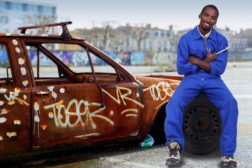 Urban mechanic with a graffitied car