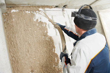 Plasterer at stucco work with liquid plaster