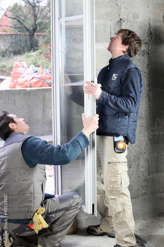 Two men installing new windows