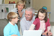 pensioners with grandchildren using computer