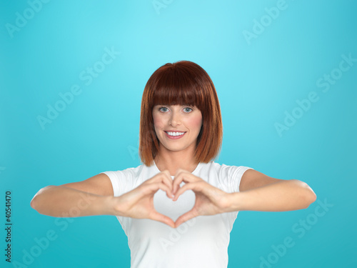 woman smiling making heart shape with hands