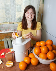 woman adding orange to juicer