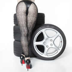 Sexy woman with High Heels playing with set of summer tyres