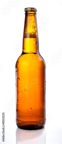Brown beer bottle with drops drink without label on a white back