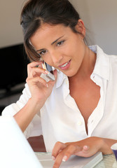 Attractive woman talking on mobile phone in front of laptop