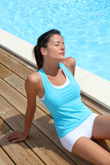 Brunette girl in fitness outfit relaxing by the pool