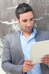Businessman using electronic tablet outside the office
