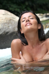 Attractive brunette woman taking a bath in river