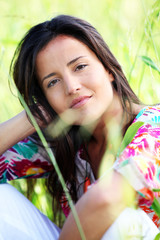 Closeup of beautiful brunette girl sitting in meadow