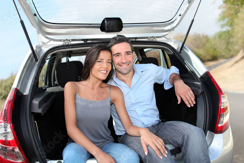 Happy couple sitting in car open trunk
