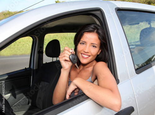 Portrait of smiling woman in car holding key