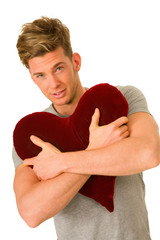 young man embracing a heart shaped pillow
