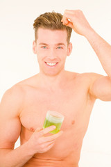 Young man applying gel on hair