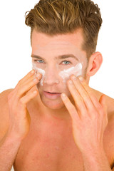 Young man applying lotion on her face