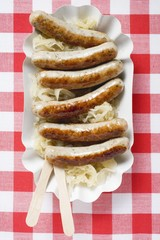 Sausages with sauerkraut on paper plate
