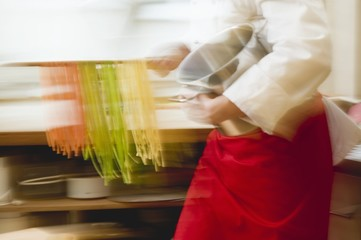 Chef with home-made coloured ribbon pasta and pasta pan