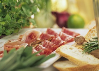 Platter of salami and ham with slices of white bread