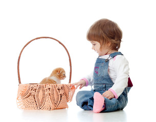 Smiling child sitting down by basket with kittens, isolated on w