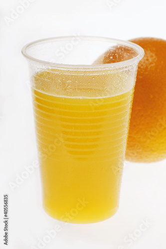 Orange juice in plastic tumbler in front of orange