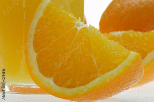 Wedge of orange in front of glass of orange juice (close-up)