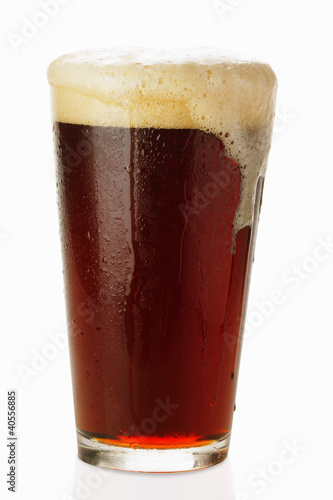 Dark beer in glass, frothing over