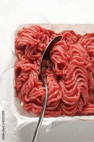 Fresh minced beef in plastic container with spoon