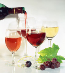 Pouring red wine; wine glasses; red grapes