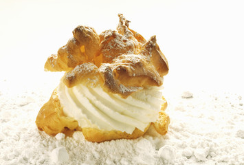 Cream puff with cream and icing sugar