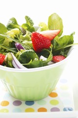 Spring salad with red onions and strawberries in bowl