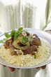 Person serving lamb ragout with almonds, raisins, couscous