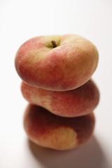 Three flat peaches, in a pile