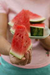 Woman holding wedge of watermelon