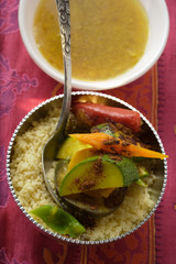 Couscous with vegetables and cinnamon in silver bowl