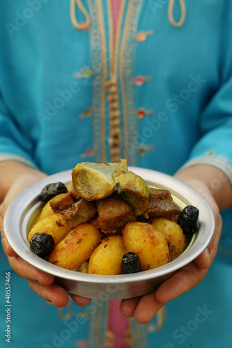 Person holding bowl of lamb ragout and potatoes (Morocco)